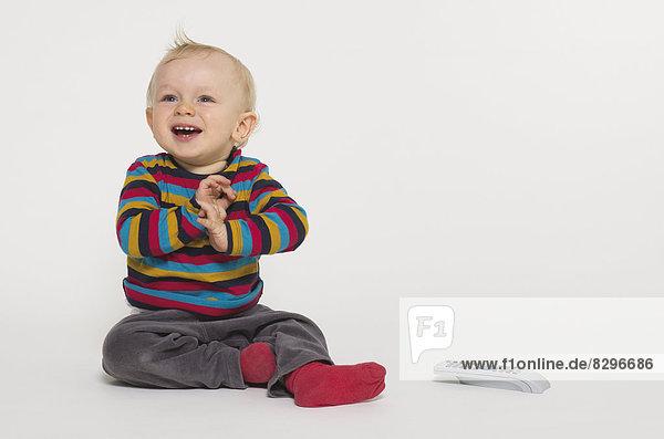 Babyboy spielt mit Fernbedienung  Studioaufnahme