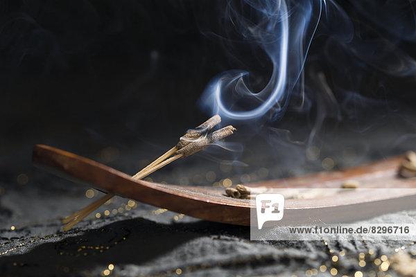 Holzhalter und Räucherstäbchen mit Rauch