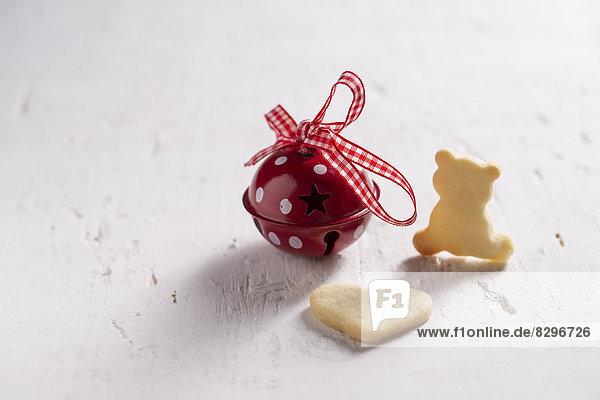 Zwei selbstgemachte Weihnachtsplätzchen und eine kleine rote Glocke  Studioaufnahme