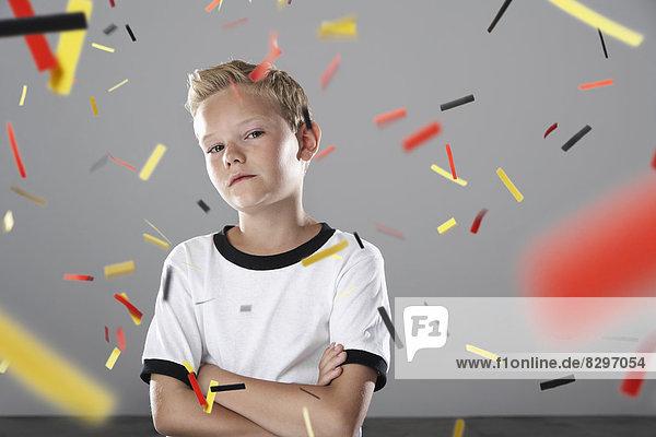 Zuversichtlicher Junge im Fußballtrikot