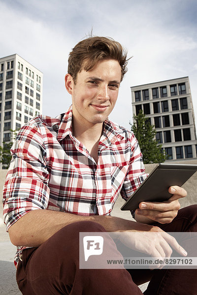 Young man with e-book outdoors