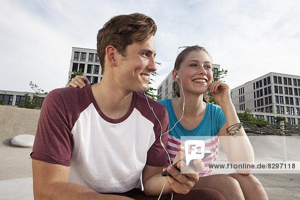 Germany  Bavaria  Munich  Couple listening to music