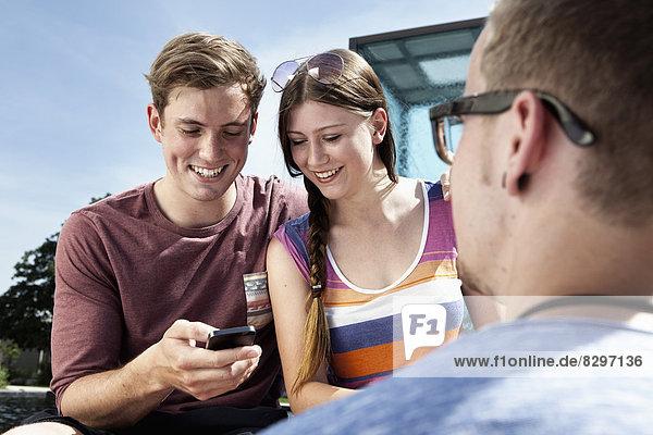 Deutschland  Bayern  München  Freunde mit Smartphone im Freien