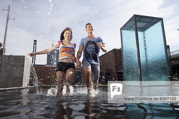 Germany  Bavaria  Munich  Couple running through water at fountain