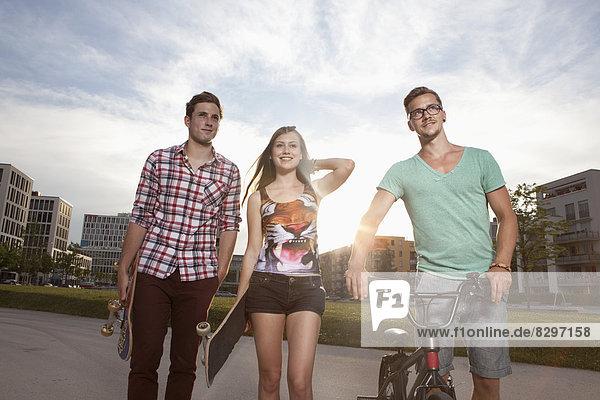 Deutschland  Bayern  München  Freunde wandern mit Skateboard und BMX Fahrrad