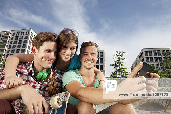 Germany  Bavaria  Munich  Three friends with smartphone taking self-portrait