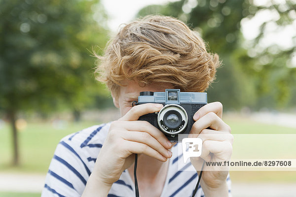 Young man taking a picture in park with an old-fashioned camera