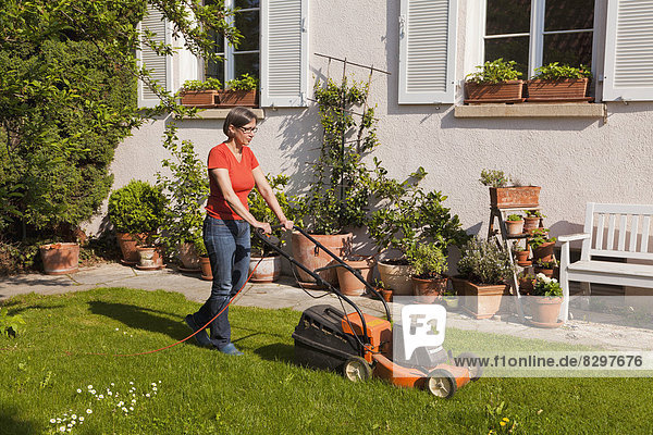 Frau beim Rasenmähen