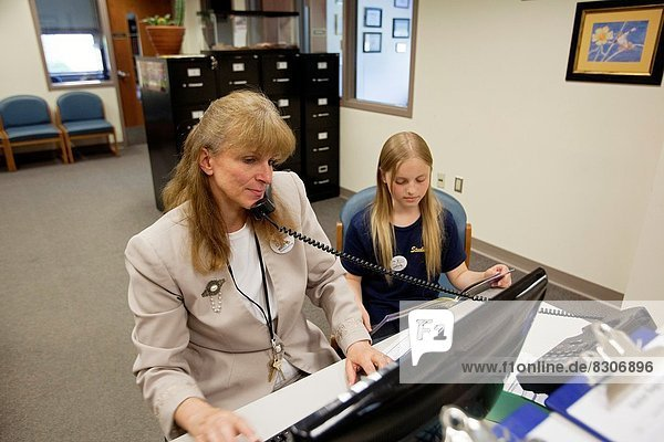 West Branch  Michigan – Surline Middle School secretary Karyn Randall works at her desk. Her daughter  Kaitlin  11  reads a book while waiting for her mother to get off work. School support staff are members of the United Steelworkers Union.