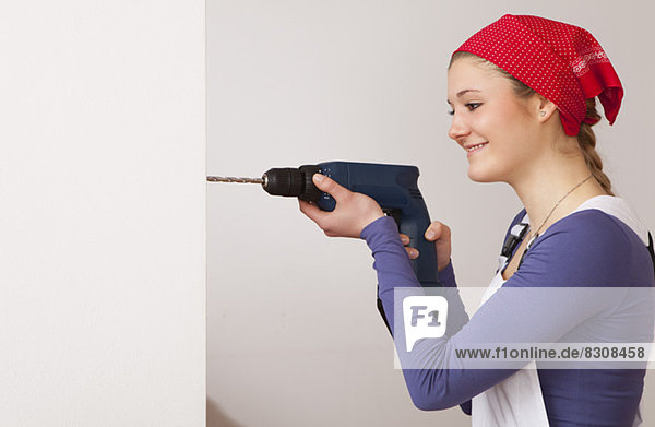 junge Frau junge Frauen benutzen Jugendlicher Wohnhaus Heimwerker Bohrmaschine Bohrer schnurloses Telefon