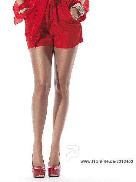 Frauenbeine in roten Shorts und roten Highheels