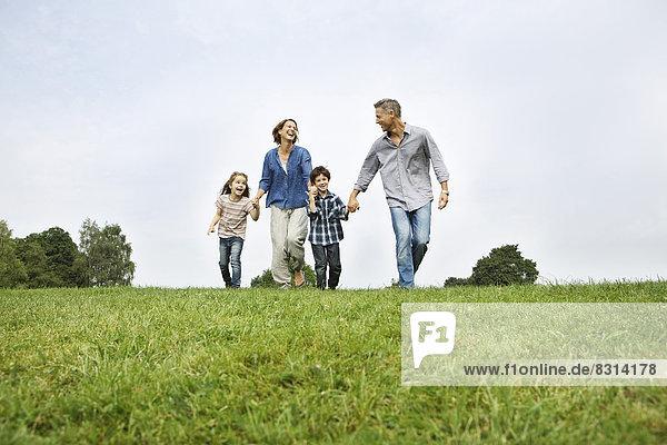 Happy family walking on meadow