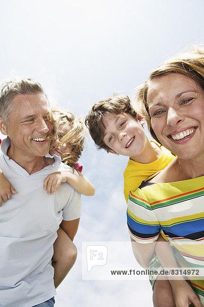 Glückliche Eltern tragen ihre Kinder huckepack