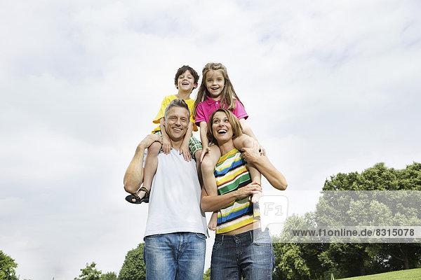 Glückliche Eltern tragen ihre Kinder im Park