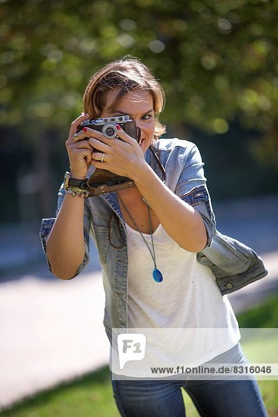 Portrait of woman with old camera taking pictures.