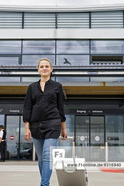 Frau mit Metallkoffer am Flughafen