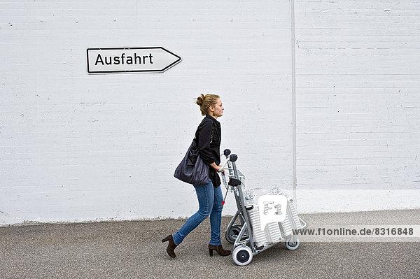 Woman pushing baggage cart under German exit sign