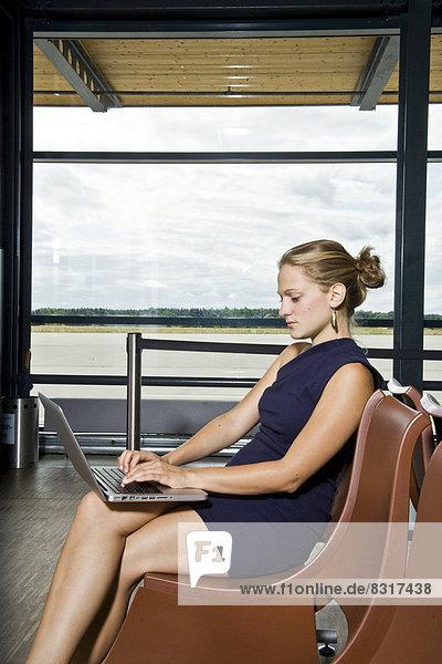 Junge Frau benutzt einen Laptop am Flughafen