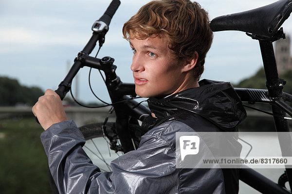 Junger Mann trägt ein Fahrrad