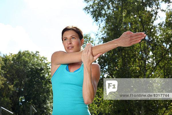 Junge Frau macht eine Dehnübung im Freien