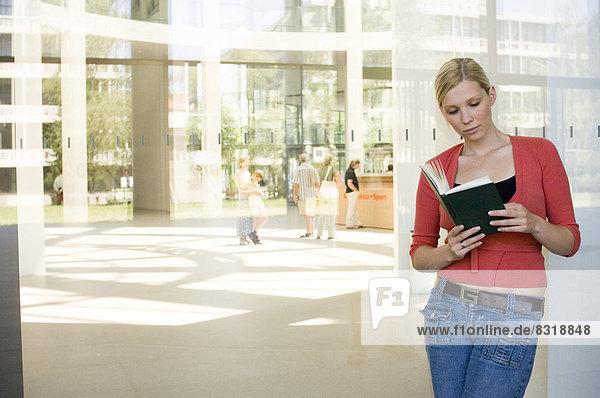 angelehnt  Frau  Buch  Glaswand  jung  Taschenbuch  vorlesen