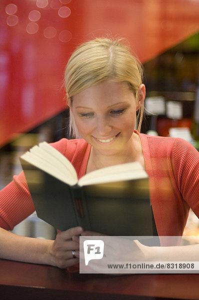 Lächelnde junge Frau liest ein Buch hinter einer Fensterscheibe