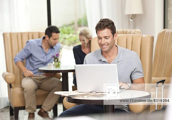 Mann mit Laptop in Hotellobby