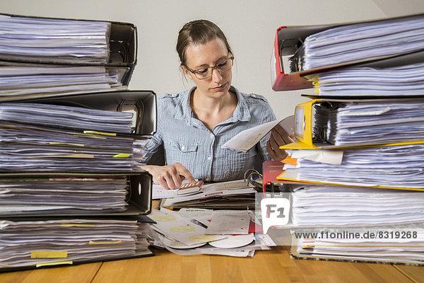 Frau arbeitet am Schreibtisch zwischen Stapeln von Akten