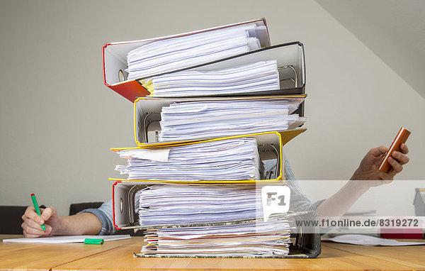 Frau arbeitet am Schreibtisch hinter einem Stapel Akten