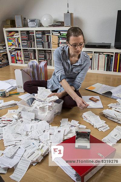 Frau sortiert Belege  Unterlagen  Rechnungen und Kassenbons auf dem Boden  für die Steuererklärung