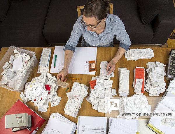 Frau sortiert Belege  Unterlagen  Rechnungen und Kassenbons auf einem Schreibtisch  für die Steuererklärung