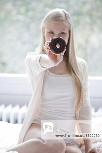 Blonde junge Frau mit Donut im Bett