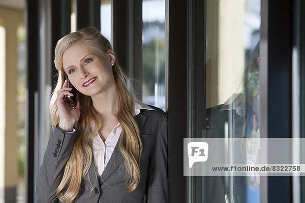 Lächelnde Geschäftsfrau telefoniert mit Handy