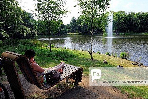 D-Oberhausen  Ruhr area  Lower Rhine  Rhineland  North Rhine-Westphalia  NRW  Kaisergarten  park  pond  fountain  woman sits on a park bench.