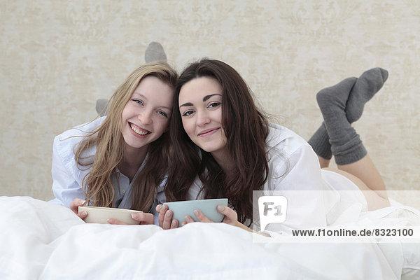 Zwei fröhliche junge Frau liegen im Bett