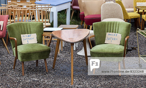 Tisch und Sessel aus den 60er Jahren werden auf einem Trödelmarkt zum Kauf angeboten Tisch und Sessel aus den 60er Jahren werden auf einem Trödelmarkt zum Kauf angeboten