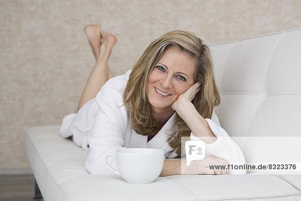 Lächelnde reife Frau mit Kaffeebecher