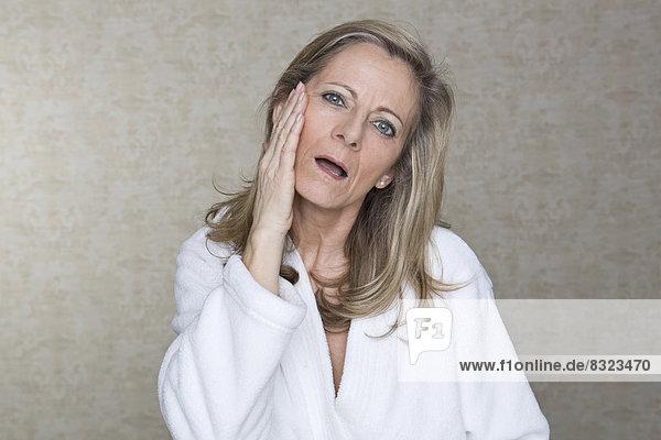 Reife Frau im Bademantel berührt ihre Wange