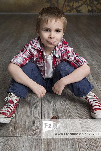 Junge sitzt auf dem Fußboden und isst Schokolade Junge sitzt auf dem Fußboden und isst Schokolade
