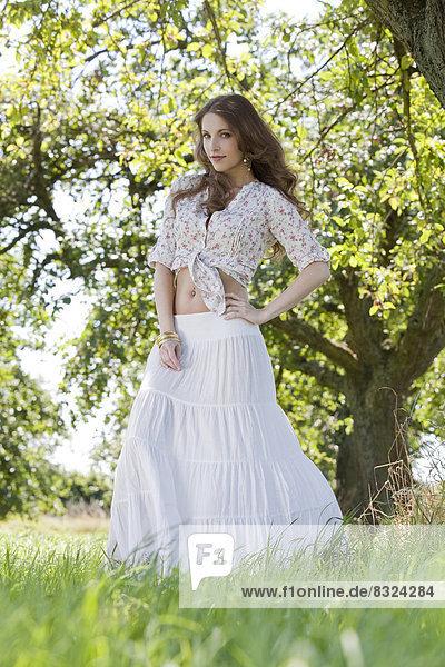Attraktive brünette Frau steht auf einem Feld