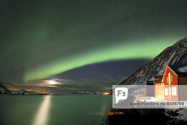Rote Fischerhütten an Fjord im Winter mit Polarlicht