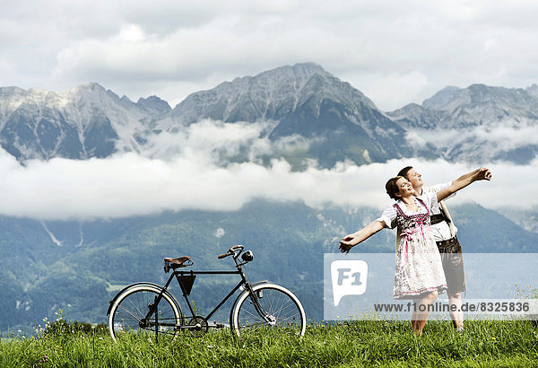 Mann und Frau in Tracht mit einem alten Fahrrad in der Natur