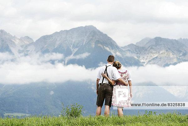 Mann und Frau in Tracht blicken auf die Berge