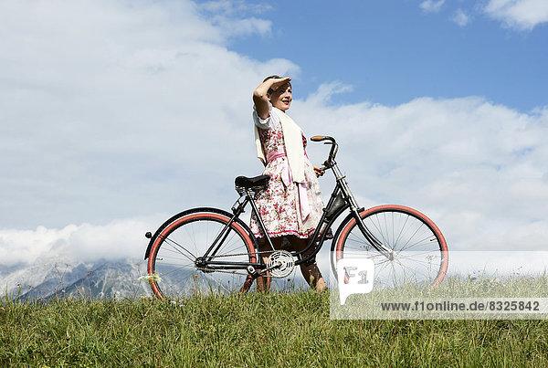 Frau im Dirndl mit einem alten Fahrrad Frau im Dirndl mit einem alten Fahrrad