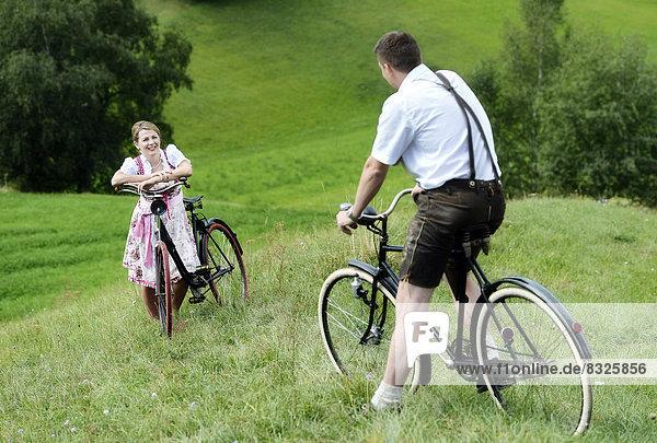 Mann in Lederhose und Frau in Dirndl auf alten Fahrrädern in der Natur