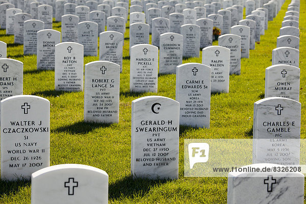 The Islamic star and crescent symbol on a tombstone  surrounded by grave markers showing the Christian cross  at the Great Lakes National Cemetery