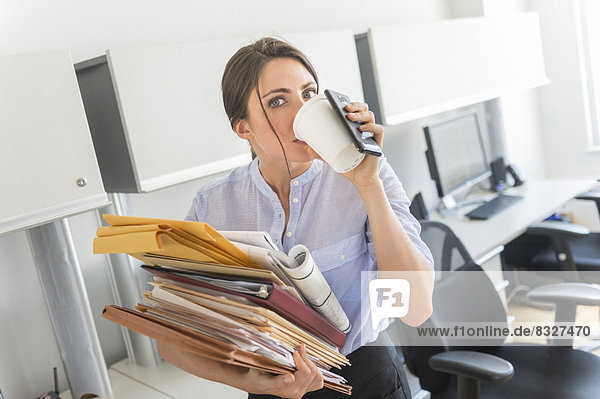 Business woman holding stack of documents and drinking coffee