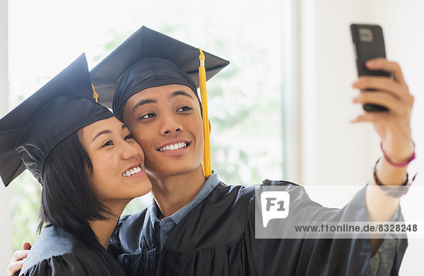 Portrait of young woman and young man wearing graduation gown