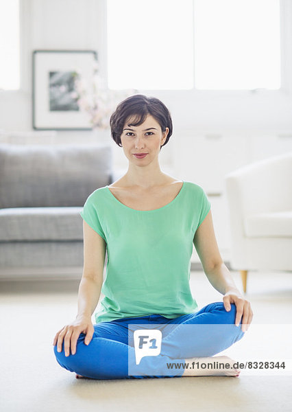 Junge Frau sitzt auf dem Fußboden,  fully_released