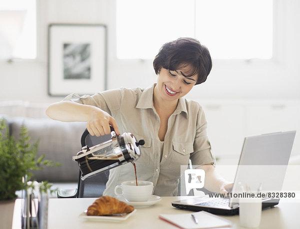 Portrait  Frau  Notebook  eingießen  einschenken  frontal  Kaffee